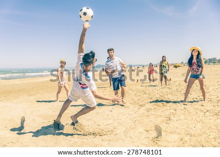 Group of multiethnic friends playing soccer on the beach - Football match on the sand on summertime - Tourists having fun on vacation with beach games - stock photo