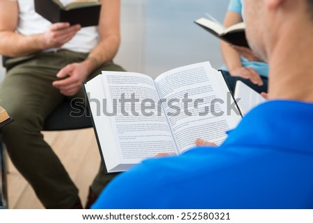 Group Of Multiethnic Friends Reading Bible Together - stock photo
