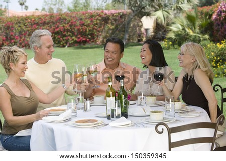 Group of multiethnic friends toasting drinks at dinner table in garden - stock photo