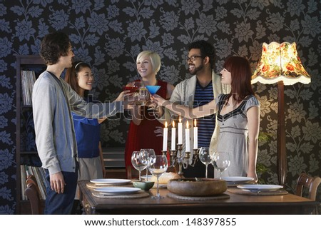Group of multiethnic friends toasting drinks by dining table - stock photo