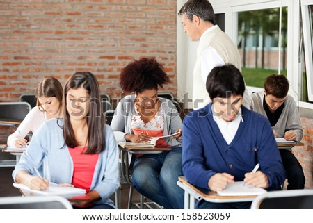Group of multiethnic students writing exam while teacher supervising them in classroom - stock photo