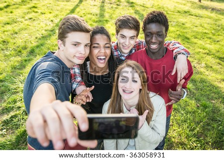 Group of multiethnic teenagers taking a selfie at park. - stock photo