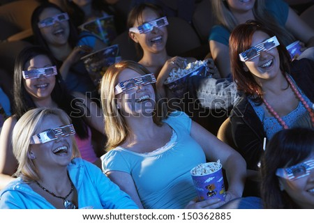 Group of multiethnic women watching 3D movie in theater - stock photo