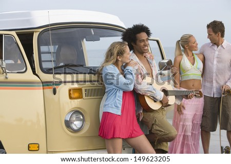Group of multiethnic young people with campervan - stock photo