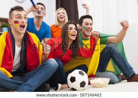 Group of multinational people cheering football match at home  - stock photo