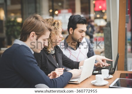 Group of multiracial business people working sitting in a bar having a coffee, connected with technological devices like smart phone, tablet and notebook - technology, working, business concept - stock photo