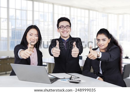 Group of multiracial business team showing thumbs up and smiling at the camera in the office - stock photo
