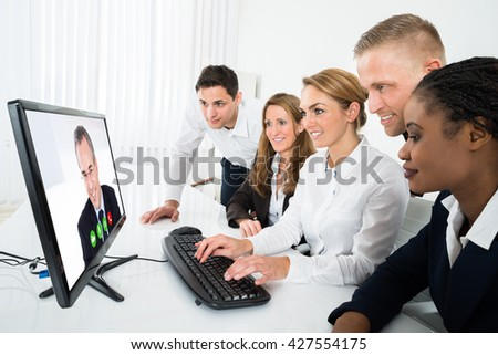 Group Of Multiracial Businesspeople Videoconferencing On Computer In Office - stock photo