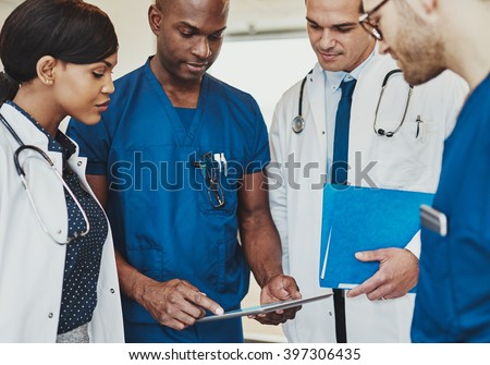 Group of multiracial doctors standing consulting patient records on a tablet computer, close up view - stock photo