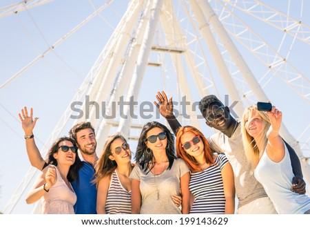 Group of multiracial happy friends taking a selfie at ferris wheel - International concept of happiness and multi ethnic friendship all together against racism for peace and fun - stock photo