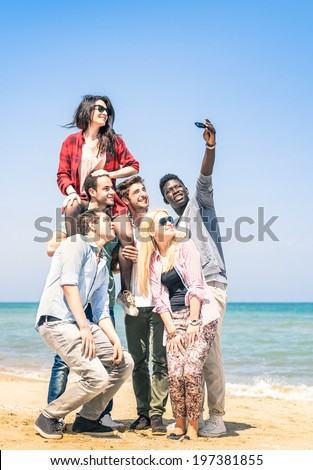 Group of multiracial happy friends taking a selfie at the beach - Concept of international friendship all together against racism - stock photo