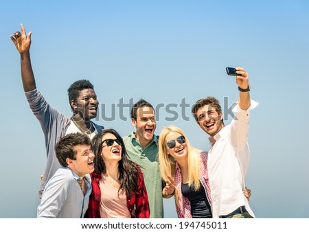 Group of multiracial happy friends taking a selfie on a blue sky - International concept of happiness and multi ethnic friendship all together against racism for peace and fun - stock photo