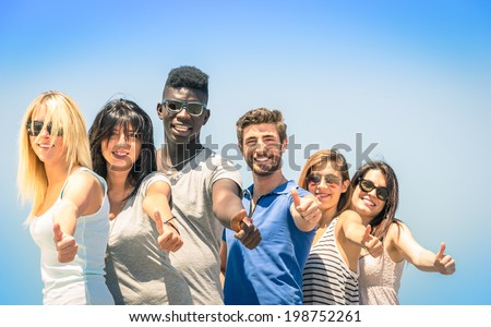 Group of multiracial happy friends with thumbs up - Concept of international friendship and success against racism and multiethnic social barriers - stock photo