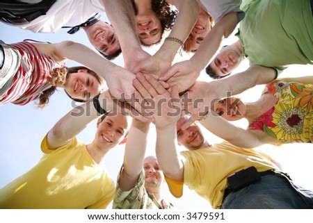 Group of nine friends keep for hands - stock photo