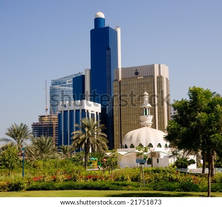 Group of office skyscrapers in Abu Dhabi with a small mosque in the foreground - stock photo