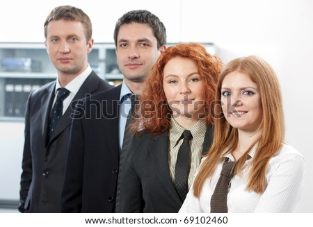 Group of office workers in business suit posing for camera in front of office building. Happy two women and men looking at photographer as confident and executive managers.