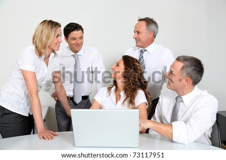 Group of office workers in front of laptop computer - stock photo