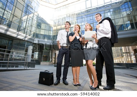 Group of office workers staying in front of modern business building in full length. Serious people posing outdoors after hard working day. - stock photo
