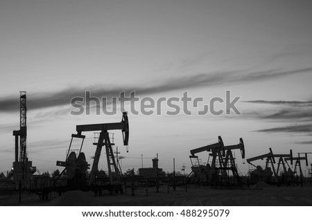 Group of oil rig and derrick silhouette during sunset in the oilfield. Oil and gas concept. Black and white.