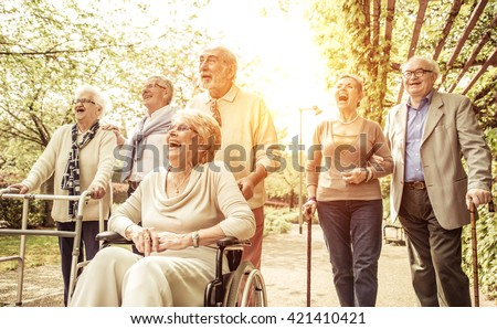 Group of old people walking outdoor. Crew with old friends, walking in the park - stock photo