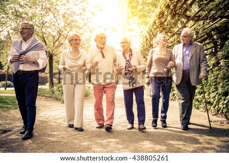 Group of old people walking outdoor. Old friends walking in a park during a sunny day - stock photo