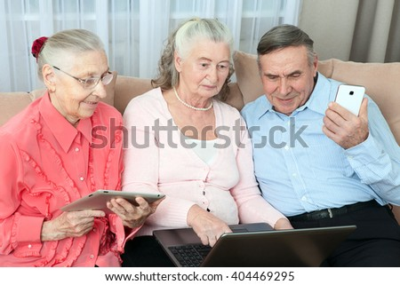 Group of older people holding a laptop, smartphone, tablet and make purchases over the Internet in the cozy living room of the house. Elderly people communicate fun.