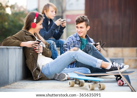 Group of ordinary teenagers relaxing with mobile phones outdoor. Focus on girl