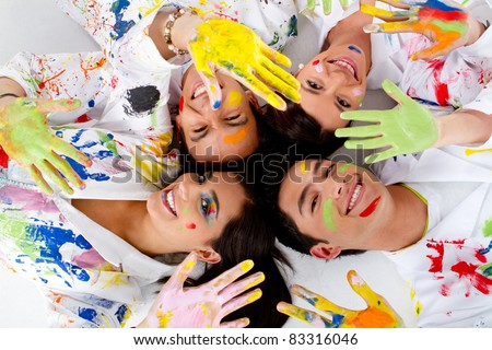 Group of painters lying on the floor showing their dirty hands and smiling