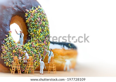 Group of painters painting over huge donut. Macro photo - stock photo