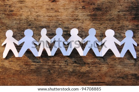 Group of paper chain people holding hands on the wood background - stock photo