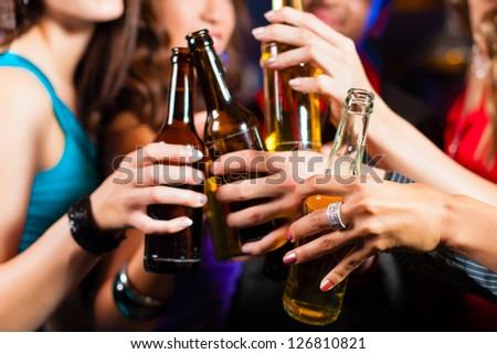 Group of party people - men and women - drinking beer in a pub or bar - stock photo