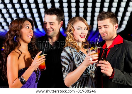 Group of party people with cocktails in a bar or club having fun - stock photo
