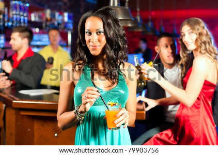 Group of party people with cocktails in a bar or club having fun; one woman is looking into the camera - stock photo