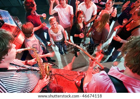 Group of partying people near a stage in a club with two musicians performing - stock photo