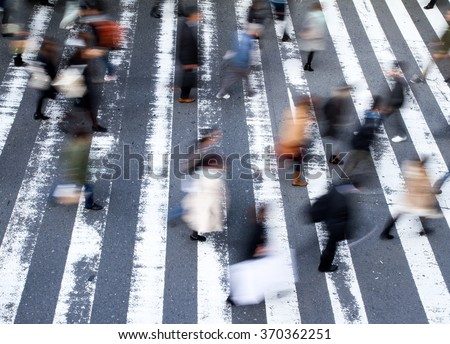 Group of pedestrians crossing the street at a zebra crossing with motion blur to the people and focus to the markings on the road, high angle view - stock photo