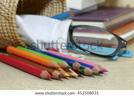 group of pencil on wooden desk with books and glass ,colorful of pencil - stock photo
