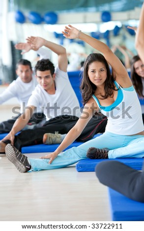 Group of people at a gym class stretching