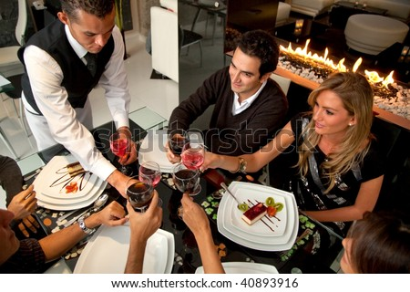 Group of people at a restaurat having dinner being served by a waiter