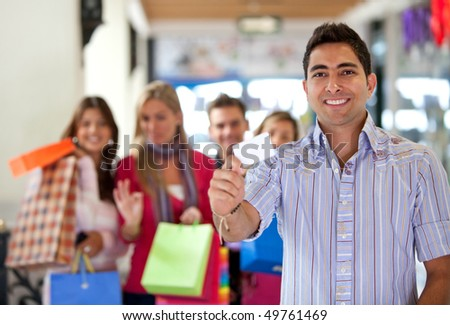 Group of people at a shopping center - man displaying a card - stock photo