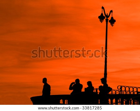 Group of people at an observation desk at twilight with red sky
