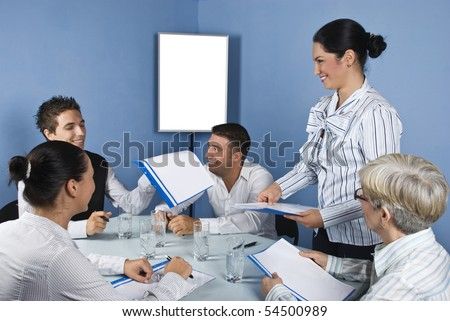 Group of people at meeting having fun and laughing while a business woman giving all folders with papers,blank chart for presentation in background