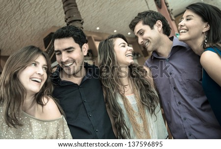 Group of people at the bar looking very happy and laughing - stock photo