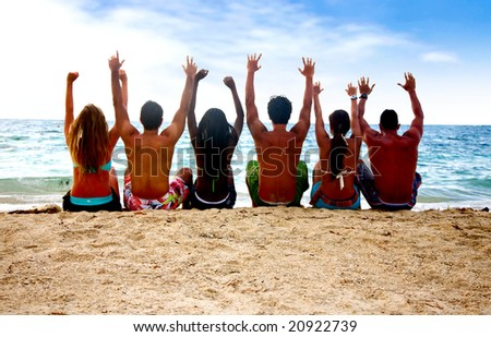 group of people at the beach with arms up - stock photo