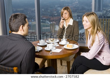 Group of People at the Cofe Table.  Short Depth of Focus (On Woman's on the Right Face). - stock photo