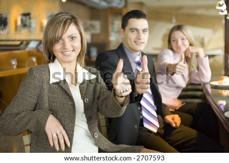 Group of People at the Cofe Table Showing OK Hand Sign. Short Depth of Focus (On First Person's Face). - stock photo