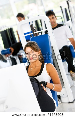 group of people at the gym doing exercise on the machines - stock photo