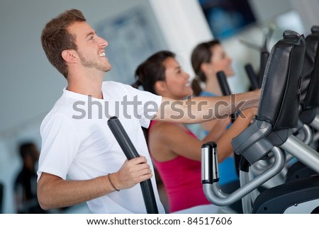 Group of people at the gym exercising on the xtrainer machines - stock photo