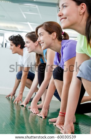 Group of people at the gym in racing position