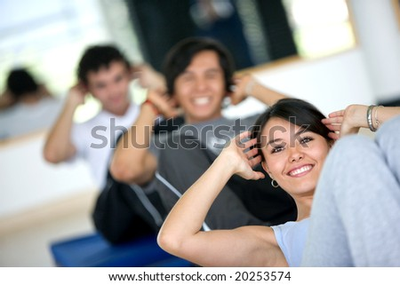 group of people at the gym smiling an doing abs exercises - stock photo