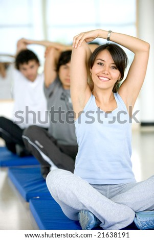 group of people at the gym smiling an doing stretching exercises - stock photo